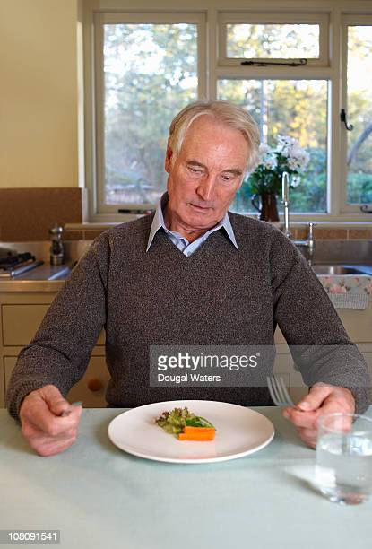 Senior man with small salad on plate.