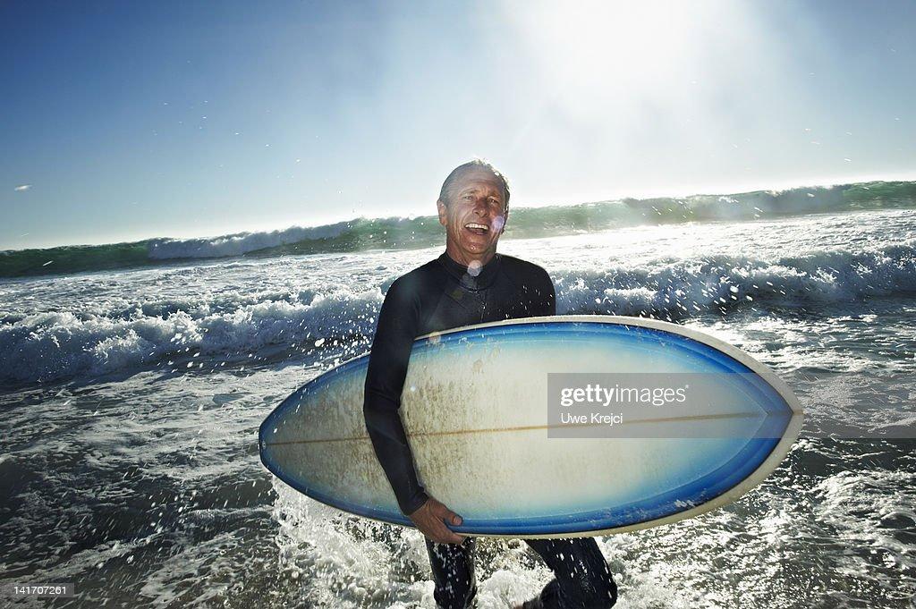Senior man with surfboard on a beach : Stock Photo