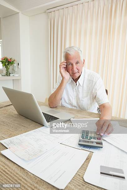 Senior man with tax documents and laptop at home