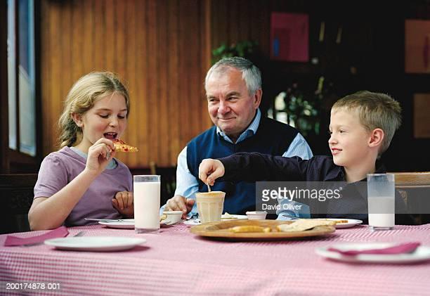 Senior man with two grandchildren at breakfast table