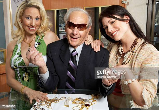 Senior man with two young women and jewellery