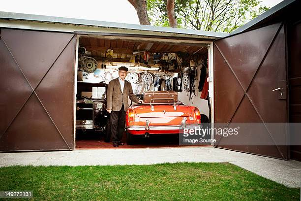Senior man with vintage car in garage