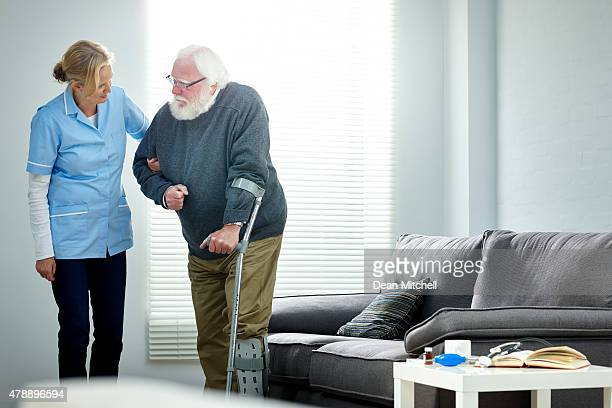 Senior man with walking stick being helped by female nurse