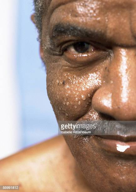 Senior man with wet face looking into camera, close-up of one side of face.