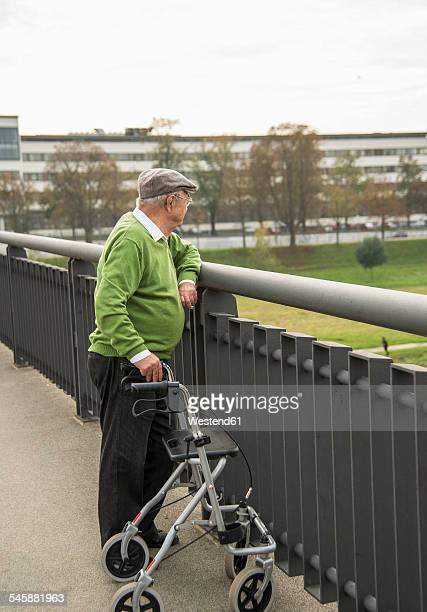 Senior man with wheeled walker on bridge