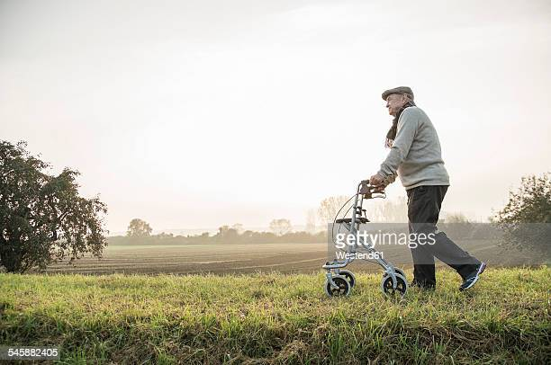 Senior man with wheeled walker walking in rural landscape