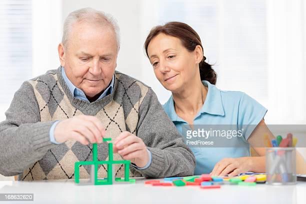 Alter Mann mit hölzernen Häuserblocks