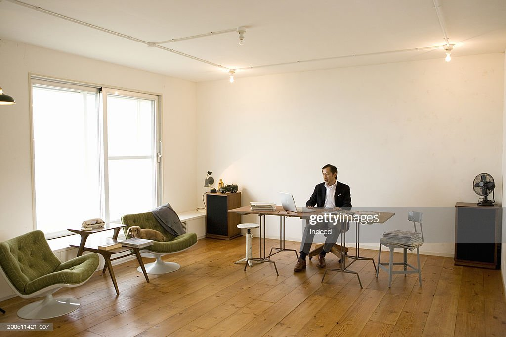 Senior man working at desk in spacious home office : Stock Photo