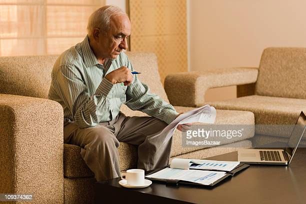 Senior man working in living room, with laptop on coffee table