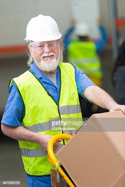 Senior hombre trabajando en el envío y almacén de distribución