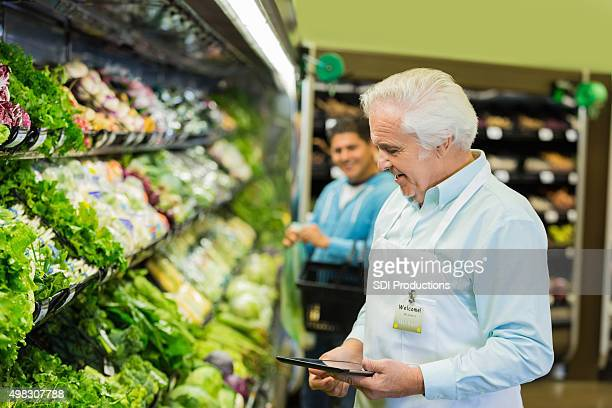 Senior man working in supermarket, taking inventory of produce