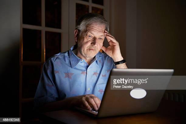 Senior man working late