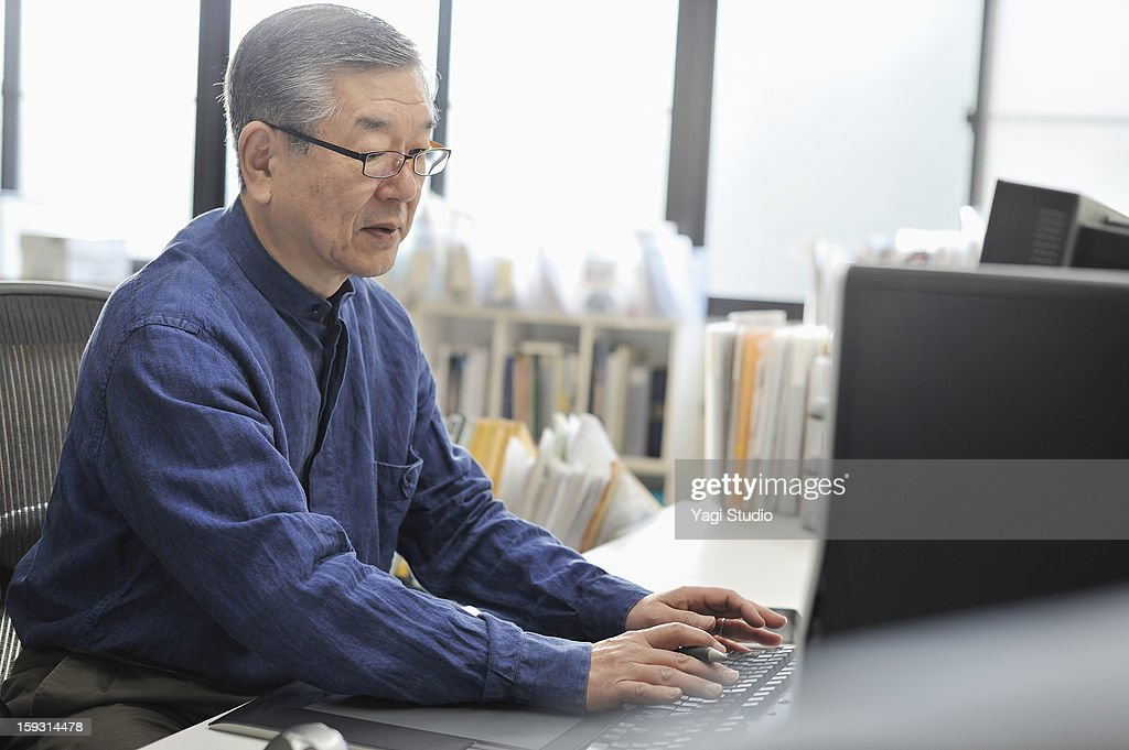 Senior man working on a computer in the office : Stock Photo