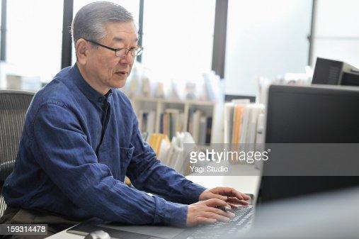 Senior man working on a computer in the office : Bildbanksbilder