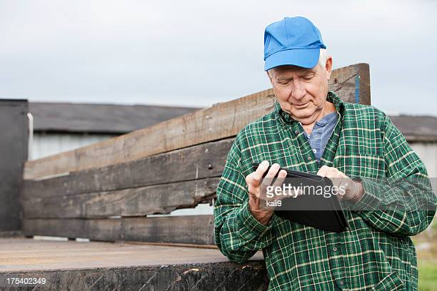 Senior man working on farm with digital tablet
