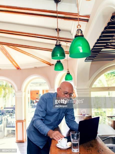Senior man working on laptop at bar counter