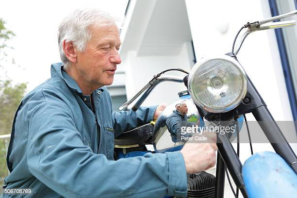 Senior man, working on old motor bike