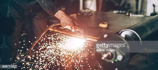 Senior man working with plasma cutter on steel plate...