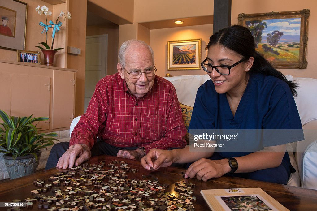 A senior man works on a puzzle as his home health care nurse helps.