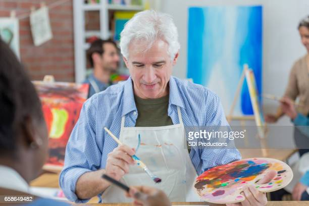 Senior man works on painting in art class