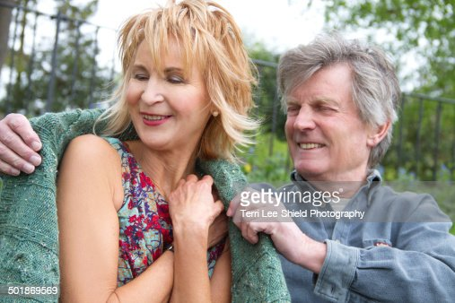 Senior man wrapping woman in warm sweater in park