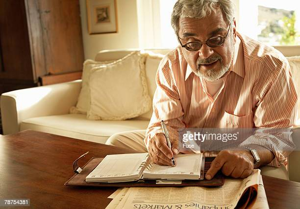 Senior Man Writing Notes from Newspaper
