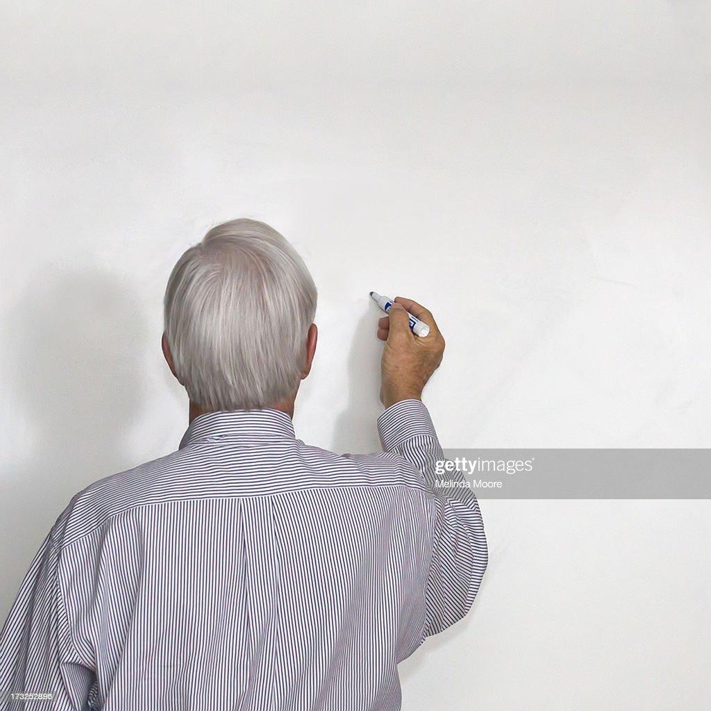 Senior Man Writing on Whiteboard : Stock Photo