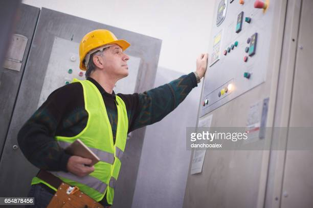 Senior manager checking machines in factory