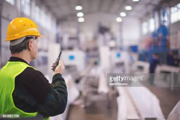 Senior manager talking on walkie talkie in factory