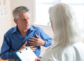 A doctor listens to a senior man patient describe chest pain.  See my portfolio for more in this series.