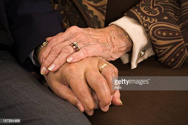senior married couple holding hands closeup: sixty years of fidelity
