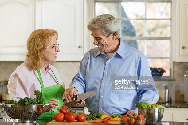 Senior married couple preparing meal together at home in kitchen
