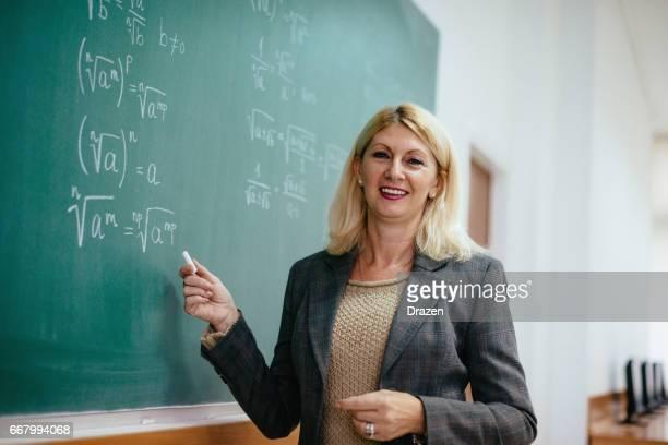Senior-Mathematik-Professor im Hörsaal in der Nähe von der Tafel mit Formeln