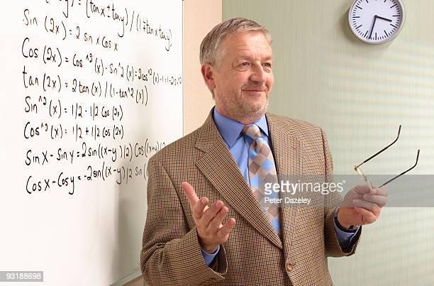 Senior maths teacher in front of white board.