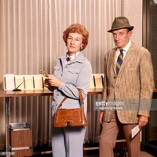 Senior Mature Middle Aged Couple Man Woman Deposit Desk Bank Banking Finance Customers Couples.