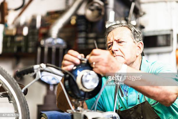 Senior mechanic fixing a motorcycle
