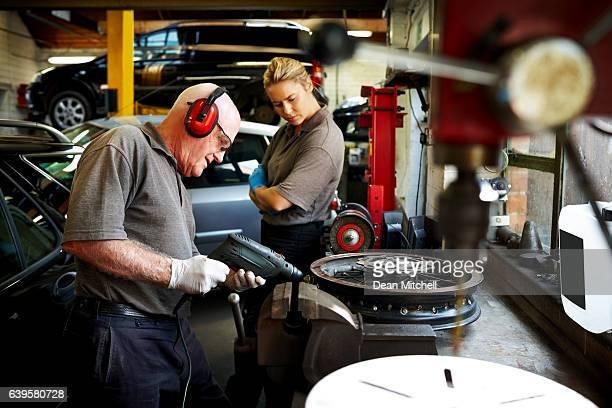 Senior mechanic working on car rims in garage