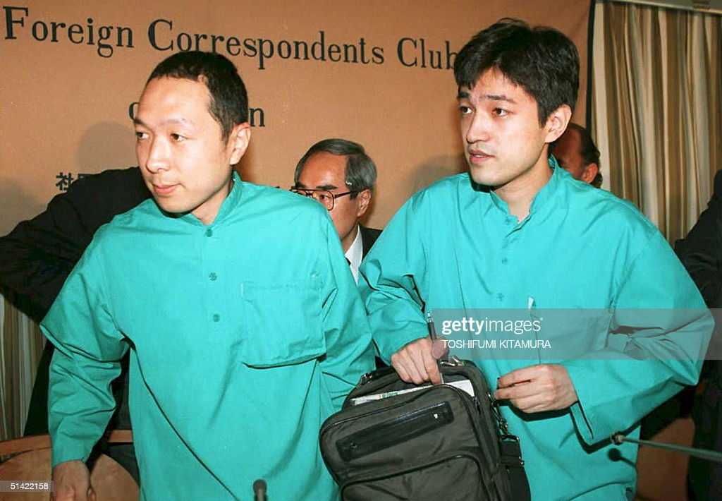 Senior members of Aum Shinrikyo (Supreme Truth) sect--Hideo Murai, head of Science & Technology (L), and spokesman Fumihiro Joyu (R)-- pack up to leave a press conference, 07 April 1995, at the Foreign Correspondents Club of Japan in Tokyo following a news conference. Murai said that all the chemicals found by police were stockpiled for the sect's survival when the world ended.