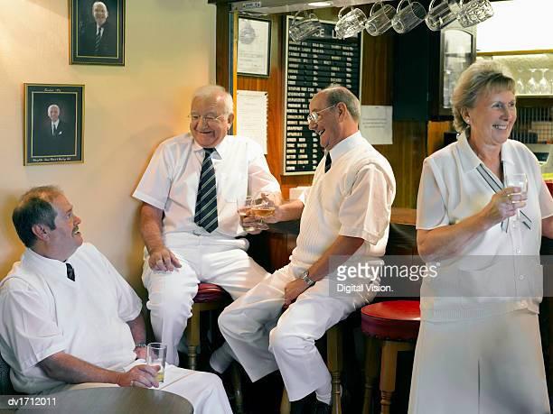 Senior Men and Women Dressed in Lawn Bowling Sportswear Enjoying a Drink in a Clubhouse Bar