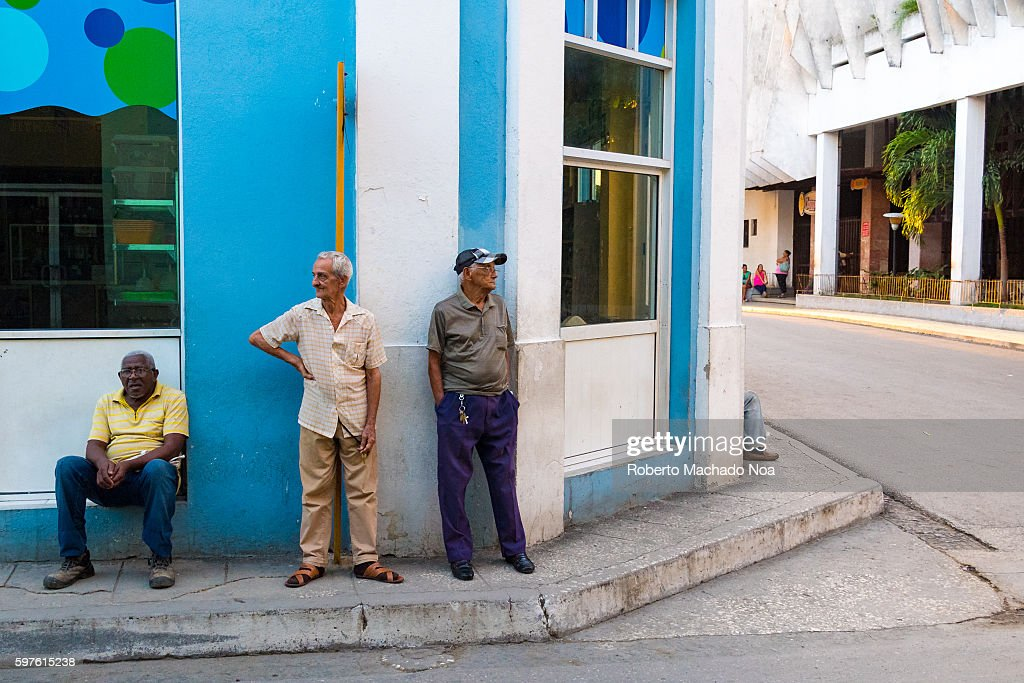 Senior men at city corner early in the morning They just chat and see things happen Cuban lifestyle or way of life
