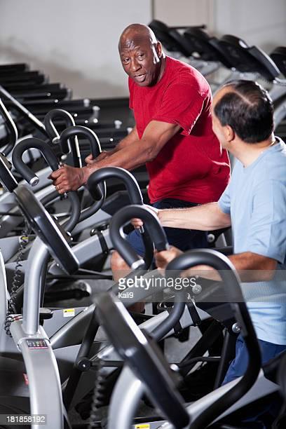 Uomini anziani all'health club ellittiche