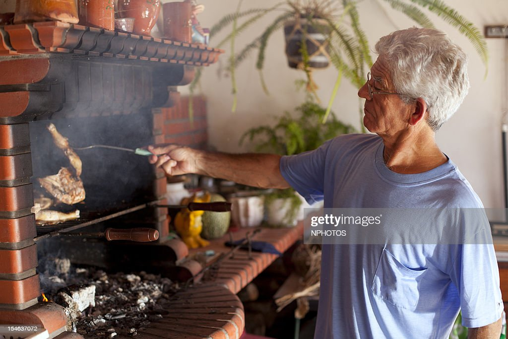 Senior men at the grill : Stock Photo