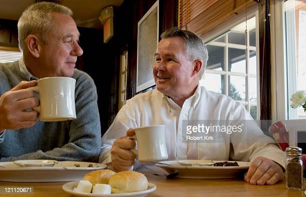 Uomini anziani mangiare e bere caffè