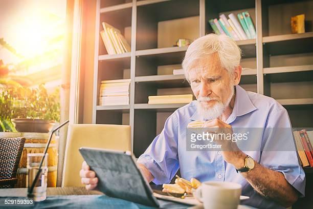 年配の男性朝食とデジタルタブレットを使用しています。