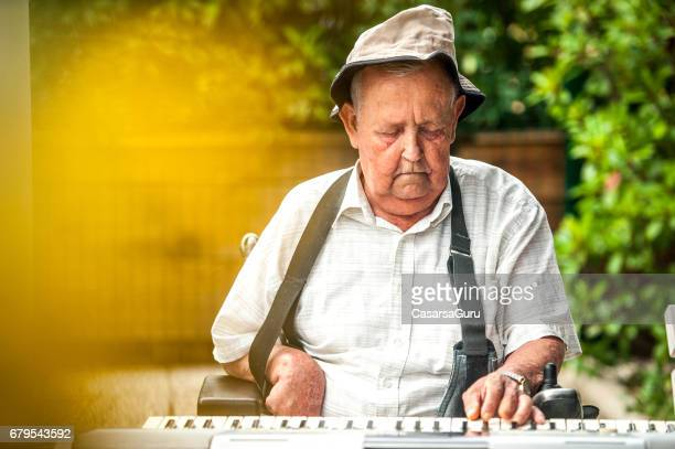 Senior Men In The Retirement Commmunity Playing Keyboard In The Garden