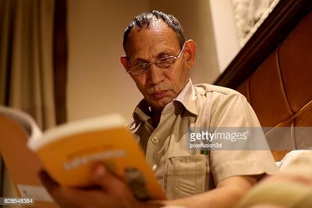 Senior men reading book