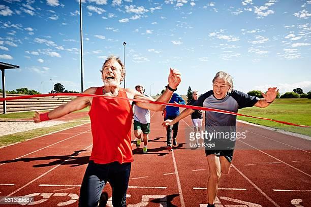 Senior men running, reaching finish line