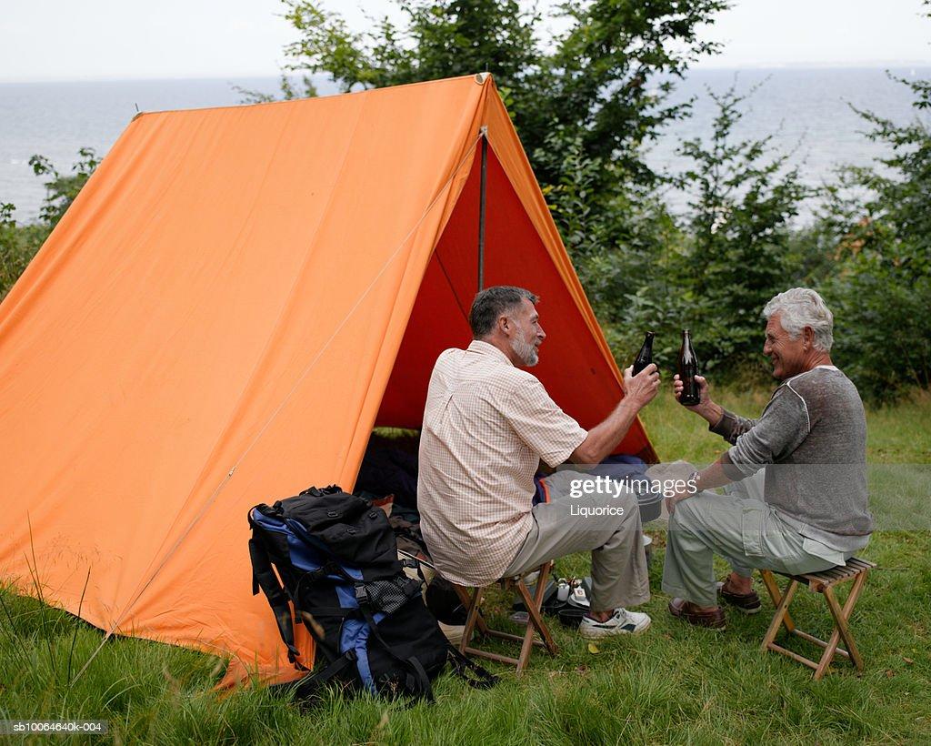 Senior men sitting outside tent, holding champagne bottle : Stock Photo
