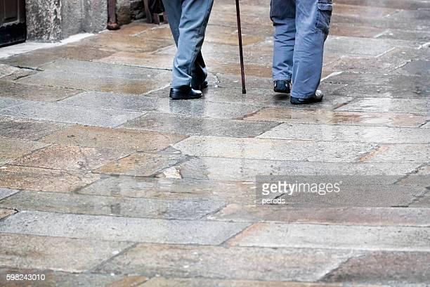 Senior men walking, rainy day, walking cane.