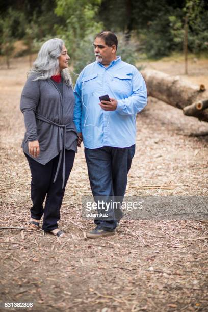 Senior Mexican Couple Using Smartphone with Headphones